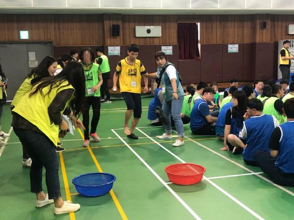 연합체육대회에서 바구니에 골넣기 놀이를 하고 있는 사람들의 모습