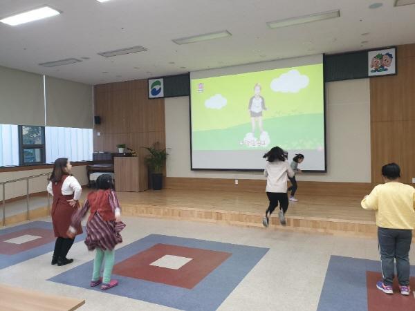 무용교실 참여아동들이 스크린에 나오고 있는 영상을 보고 이리저리 뛰어다니는 모습