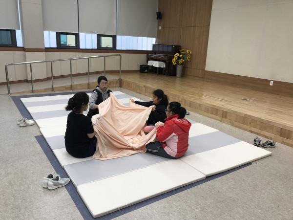 강사와 아이들이 둥글게 앉아 천을 활용한 활동을 진행하는 모습